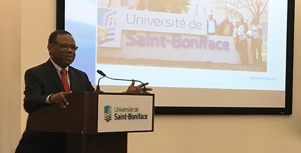 Jean Elie Larrieux, président du CREFI-Haïti au podium lors d'une conférence de presse