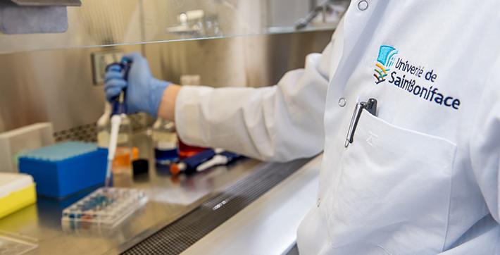 Un scientifique travaille un projet de recherche sous une hotte dans un laboratoire