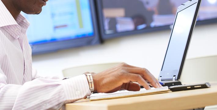 Un homme qui travaille à un ordinateur portatif.