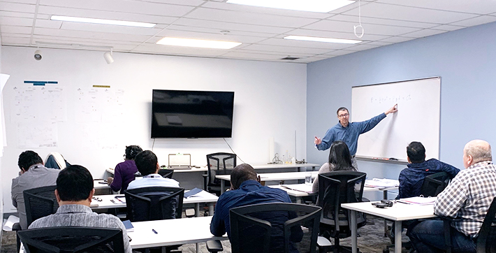 Chemistry professor François Gauving teaching a group of Roquette employees.