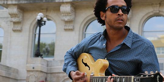 Jérémie Brémault avec sa guitare sur les marches de l'USB