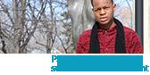 Cheick Keita, étudiant à l'USB et rappeur, debout devant le monument de Louis Riel