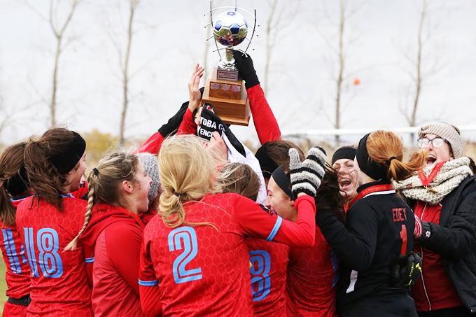 L'équipe de soccer féminin des Rouges hissent la coupe de la ligue MCAC.