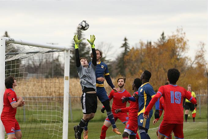 Les Rouges de l'USB et les Bobcats de Brandon University en demi-finale de soccer de la MCAC. Un gardien de but saute pour attraper la balle.